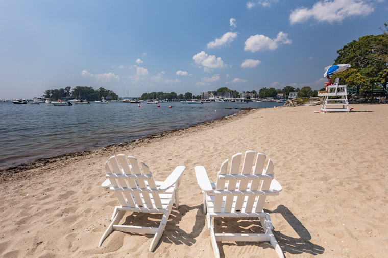 beach with adirondack chairs